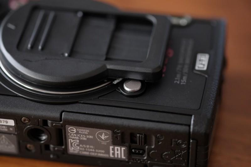 TG-5用UN製レンズプロテクトキャップ|レンズリング取り外しボタンにかかる